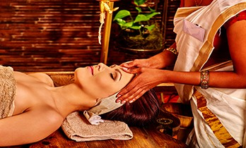 Woman having facial ayurveda spa treatment in Indian salon.