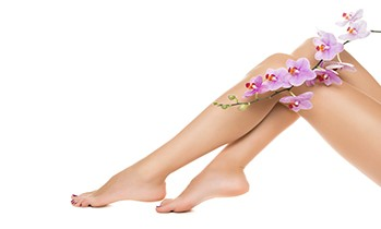 Healthy female Legs. Spa. Long woman legs and orchids